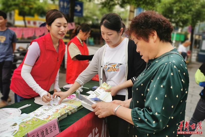 社区计协志愿者向居民发放卫生健康知识手册.jpg